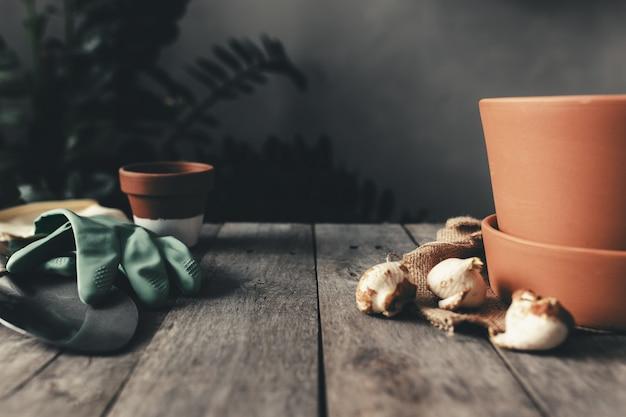 Vasi in ceramica sul vecchio tavolo in legno grigio, bulbi di tulipani, guanti verdi, pala da giardino. foto di alta qualità Foto Premium