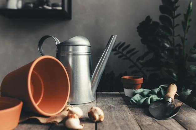Vasi in ceramica su un vecchio tavolo in legno grigio, bulbi di tulipani, annaffiatoio, guanti verdi e pala da giardino. foto di alta qualità Foto Premium