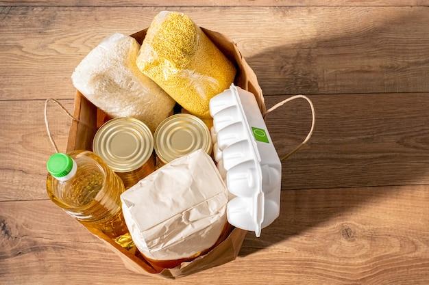 Cereali, cereali, olio, spezzatino, porridge e generi alimentari in scatola in una borsa artigianale per gli acquisti. Foto Premium