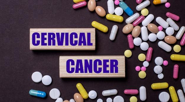 Il cancro cervicale è scritto su blocchi di legno vicino a pillole multicolori. concetto medico Foto Premium