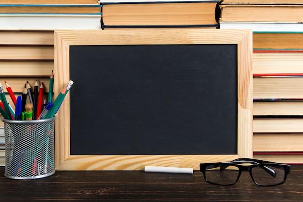 Lavagna nera, occhiali, supporto con penne, matite e gesso, contro libri, copia spazio. Foto Premium