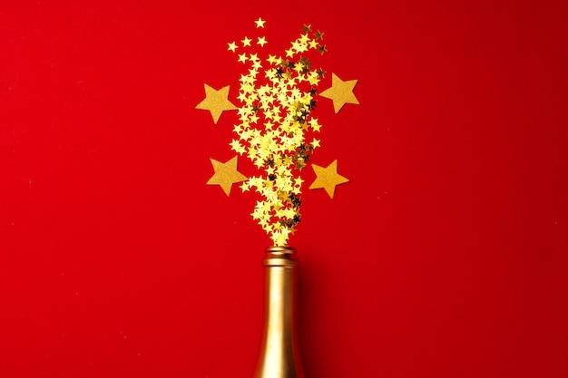 Bottiglia di champagne con coriandoli scintillanti su piatto rosso laici Foto Premium