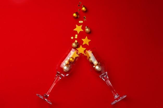 Bicchiere di champagne con coriandoli glitter su sfondo rosso piatto vista dall'alto Foto Premium