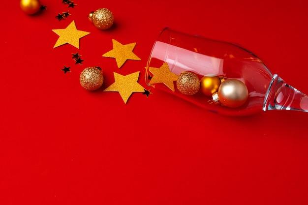 Bicchiere di champagne con coriandoli glitter su piatto rosso laici Foto Premium