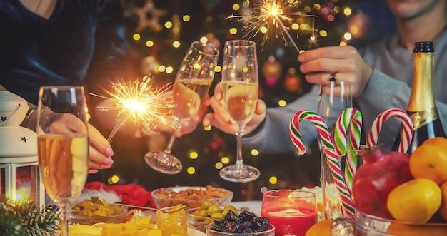 Champagne in mano contro l'albero di natale Foto Premium