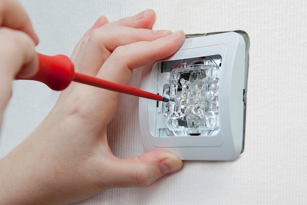 Installazione interruttore luce parete spogliatoio con cacciavite. Foto Premium