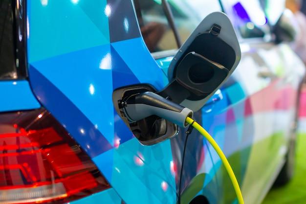 Ricarica di un'auto phev elettrica o ibrida con il cavo di alimentazione inserito. stazione di ricarica per auto elettriche Foto Premium
