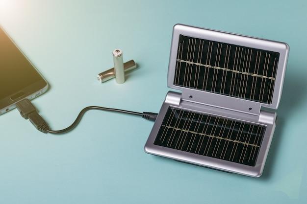 Ricarica dall'energia solare di un moderno telefono cellulare. uso dell'energia solare. tecnologia futura. Foto Premium