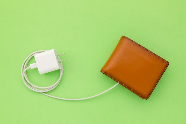 Ricarica l'alimentazione al concetto finanziario: il cavo del caricabatterie bianco con vista dall'alto si collega al portafoglio marrone Foto Premium