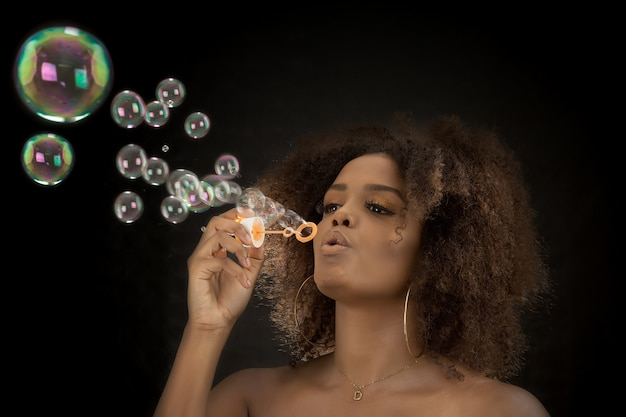 Affascinante donna nera che soffia bolle di sapone in studio Foto Premium