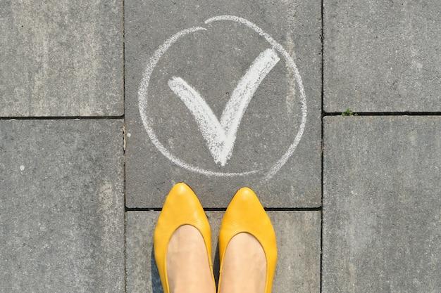 Segno di spunta ok segno sul marciapiede grigio con gambe di donna, vista dall'alto Foto Premium