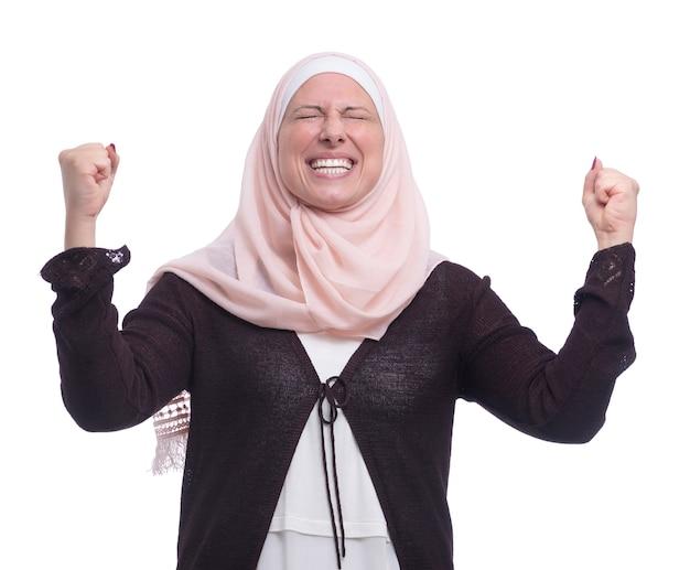 Cheeful emozionante donna musulmana che celebra il successo sul muro bianco Foto Premium