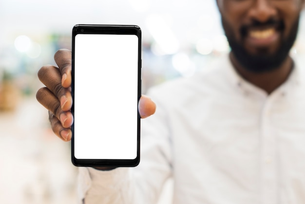 Maschio nero adulto allegro che mostra telefono cellulare su fondo vago Foto Premium
