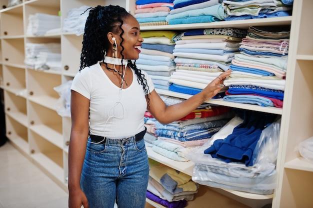 La donna afroamericana allegra sta gli scaffali vicini con gli asciugamani nella lavanderia self-service. Foto Premium