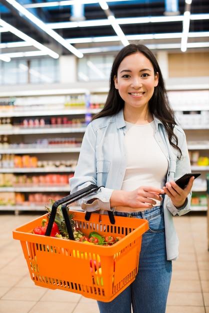 Cestino della spesa di trasporto della donna asiatica allegra nel mercato Foto Premium