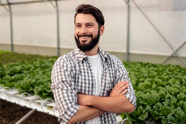 Allegro uomo barbuto in camicia a scacchi incrociando le braccia e guardando lontano con un sorriso mentre si trovava vicino al tavolo idroponico con piante in serra moderna Foto Premium