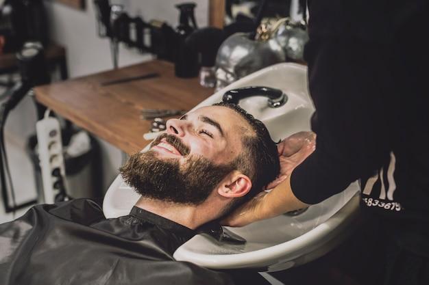 Cliente allegro che lava testa in salone Foto Premium