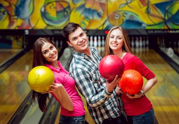 Amici allegri alla pista da bowling con le palle. Foto Premium