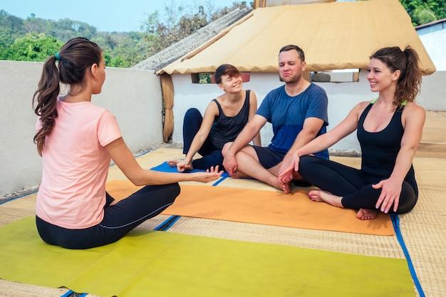 Amici allegri comunicano con un istruttore di yoga seduto sul pavimento in una lezione di yoga Foto Premium