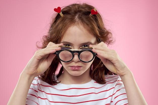 Ragazza allegra con sfondo rosa stile di vita della maglietta a strisce degli occhiali da sole delle trecce. foto di alta qualità Foto Premium