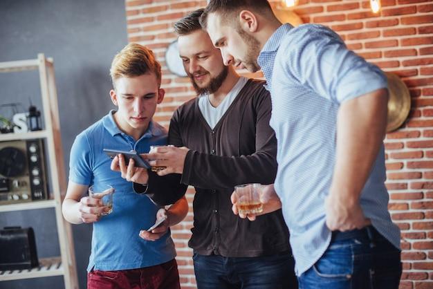 I vecchi amici allegri comunicano tra loro e guardano il telefono, bicchieri di whisky nel pub. stile di vita di intrattenimento. wifi collegato persone nella riunione del tavolo da bar Foto Premium