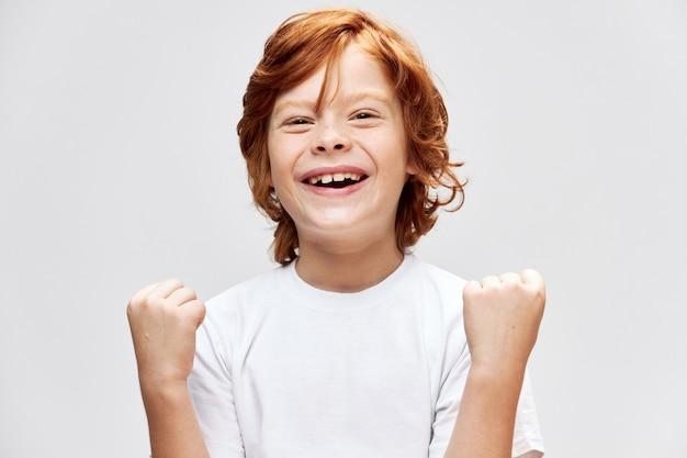 Bambino allegro della testarossa con la maglietta bianca Foto Premium