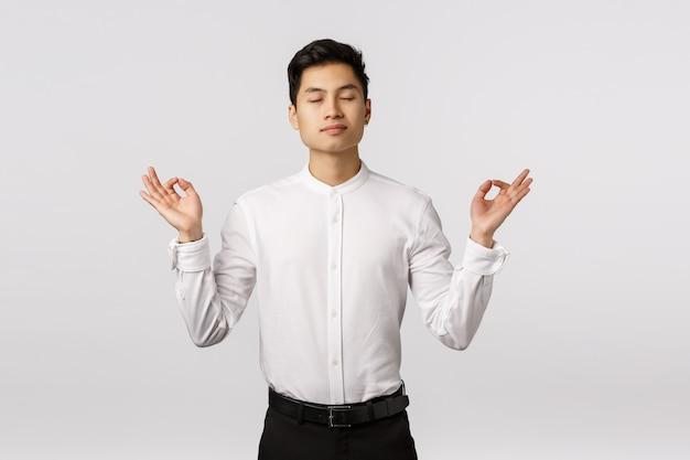 Giovane imprenditore asiatico sorridente allegro con la camicia bianca sollevata Foto Premium