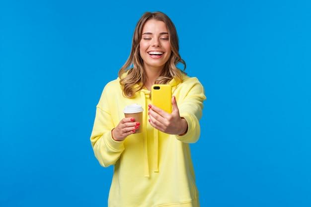 Allegro, sorridente, biondo, caucasico, femmina, blogger, registrare, video, o, prendere selfie, su, suo, telefono, ridere, e, ghignare, presa a terra, asporto, tazza caffè, stare blu muro Foto Premium