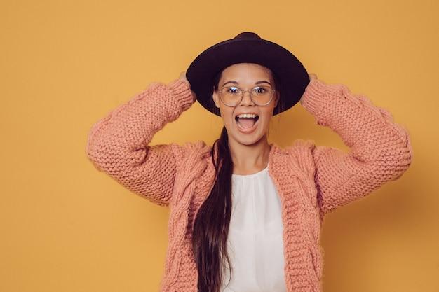 Il brunette sorpreso allegro in vetri si è vestito in maglione viola che tiene il suo cappello con la bocca spalancata, gridante. concetto di persone felici. Foto Premium