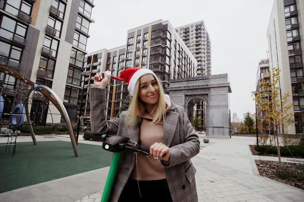 Donna allegra che fissa il cappello di babbo natale e guida lo scooter elettrico. blocchi di appartamenti sullo sfondo. una donna felice si è acquistata uno scooter elettrico in onore delle vacanze di natale. Foto Premium
