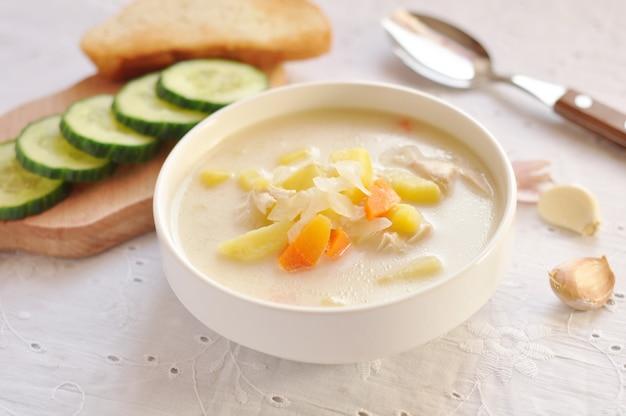 Zuppa di formaggio con pollo e verdure in ciotola bianca, cetriolo e aglio in un tovagliolo di tessuto. messa a fuoco selettiva Foto Premium
