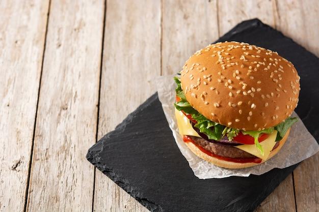 Cheeseburger con carne di manzo, pomodoro, lattuga e cipolla sulla tavola di legno Foto Premium