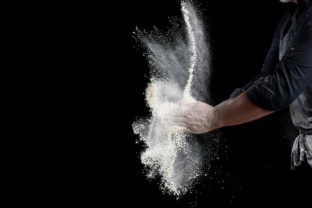 Lo chef in uniforme nera spruzza la farina di grano bianco in diverse direzioni, il prodotto disperde polvere, sfondo nero, copia spazio Foto Premium