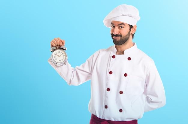 Chef in possesso di un orologio su sfondo bianco su sfondo colorato Foto Premium