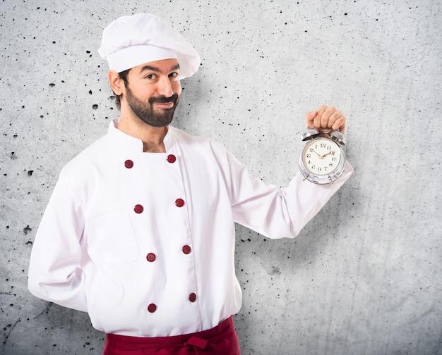Chef in possesso di un orologio su sfondo bianco Foto Premium