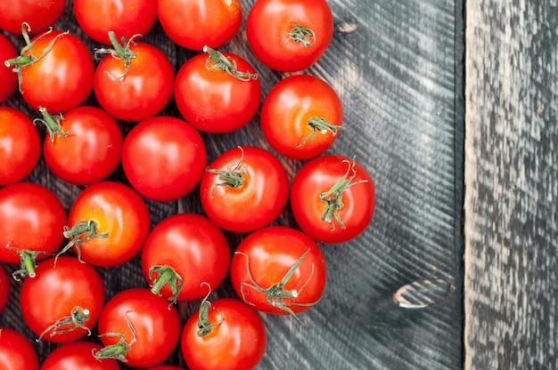 Pomodori ciliegia su vecchio fondo di legno. stile rustico. vista dall'alto Foto Premium