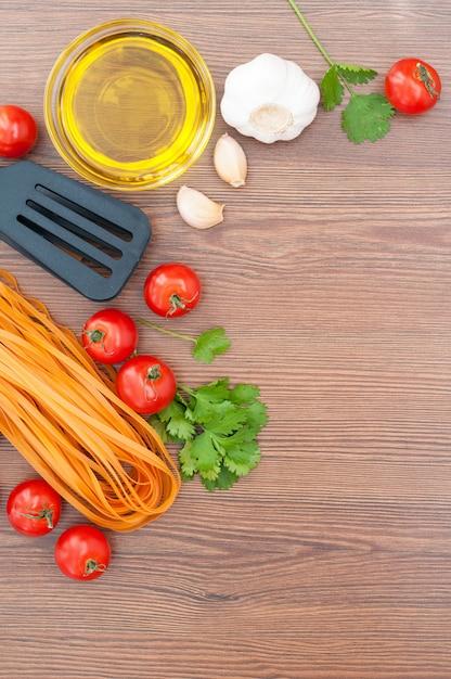 Tenaglie di pomodori ciliegia, pasta, olio d'oliva, aglio, erbe e pasta sullo sfondo in legno vecchio. stile rustico. cibo italiano tradizionale. Foto Premium
