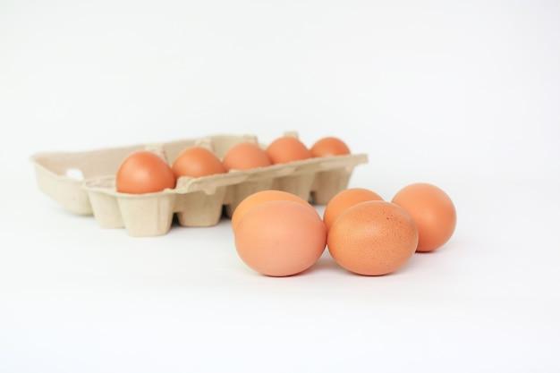 Uova di pollo marrone e scatola di cartone di uovo su bianco Foto Premium