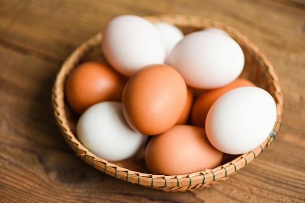 Le uova di gallina e le uova di anatra si raccolgono dai prodotti agricoli naturali in un cestino Foto Premium