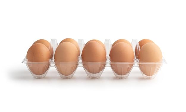 Uova di gallina nella scatola di plastica isolata sulla superficie bianca con tracciati di ritaglio Foto Premium