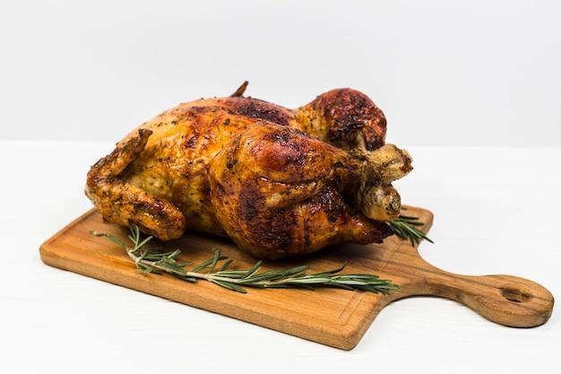 Pollo con rosmarino su bianco Foto Premium