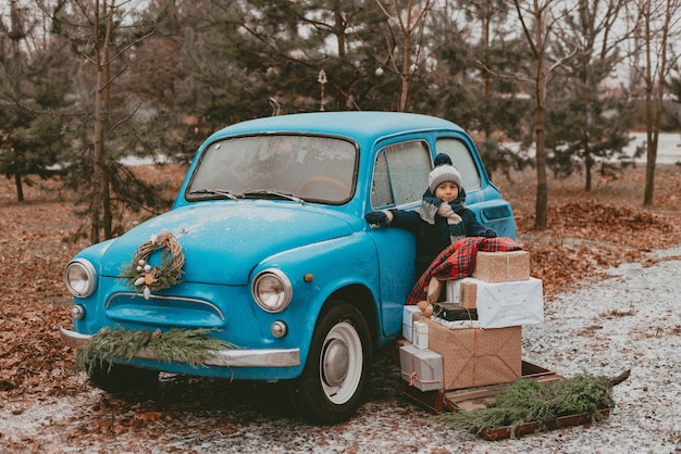 Bambino decorato con un'auto retrò blu con rami di un albero di natale festivo, scatole regalo in carta da regalo artigianale, una ghirlanda di aghi di pino e abete. viaggio di famiglia di capodanno. sogno d'infanzia, ricordi, desideri. Foto Premium