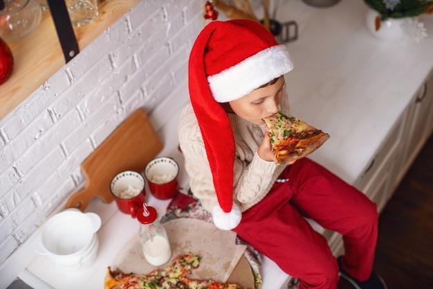 Un bambino mangia la pizza in cucina Foto Premium