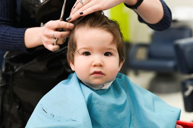 Un bambino dal parrucchiere. il primo taglio di capelli del bambino dal parrucchiere. taglio di capelli del bambino. Foto Premium