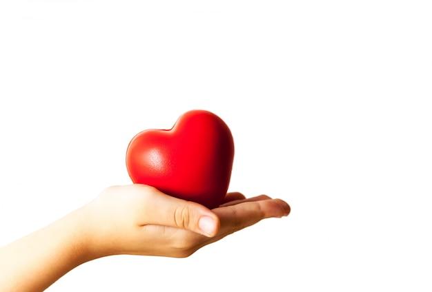 Il bambino passa la tenuta del concetto rosso di cuore, di sanità, di donazione e dell'assicurazione familiare Foto Premium
