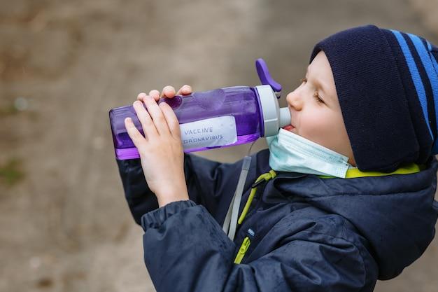 Un bambino in una maschera medica che beve acqua da una bottiglia che dice il vaccino contro il coronavirus Foto Premium