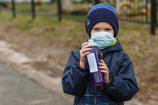 Un bambino con una mascherina medica tiene in mano una bottiglia con il vaccino coronavirus con iscrizione Foto Premium