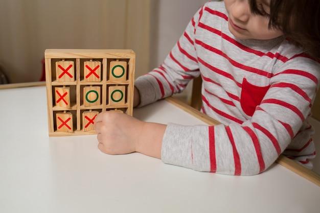 Bambino che gioca con tris in legno Foto Premium
