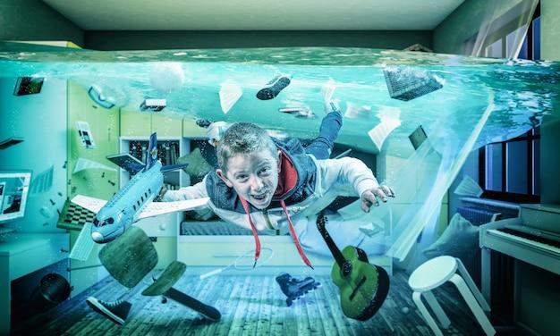 Il bambino gioca felice con un aeroplano nella sua stanza allagata. Foto Premium