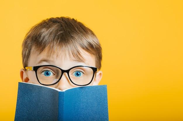 Il bambino legge un libro contro un muro luminoso Foto Premium